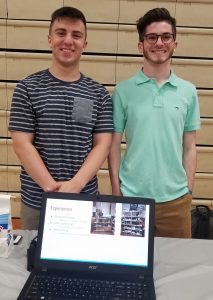 Jack and Nick standing with a computer and their PowerPoint presentation about their experiences.